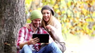 Couple looking at a digital tablet in forest video