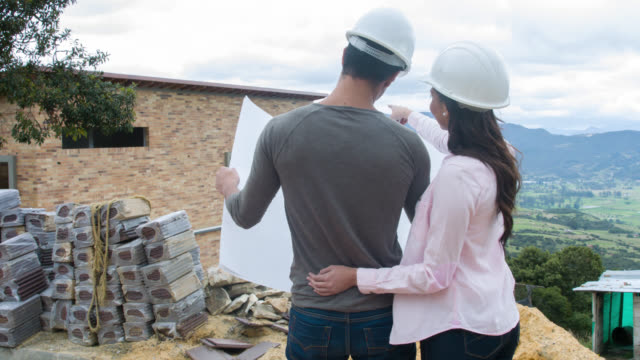 Couple looking at blueprints of their house under construction video