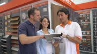 Couple looking at kitchen cabinets for a home renovation video
