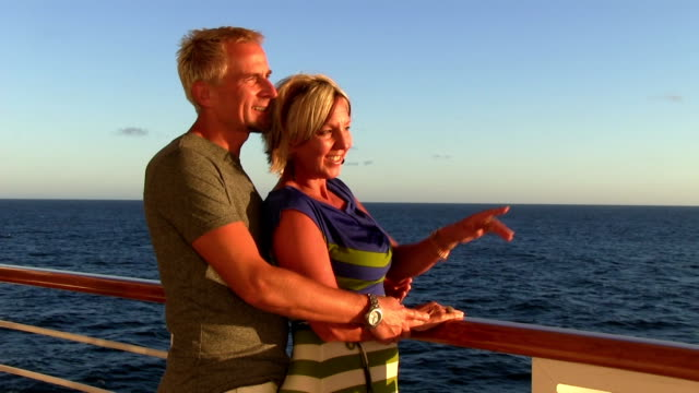 Couple looking at waves on cruise during sunset. video