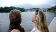 POV of couple looking out across lake to village behind video
