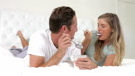Couple Lying On Bed Eating Tub Of Yoghurt video