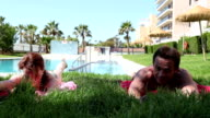 Couple making sport during holidays, exercising their back muscles video