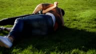Couple makng summersault, tumble and turn handsprings on grass in slow mo video