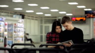 Couple, man and woman sitting in waiting room and look in tablet video