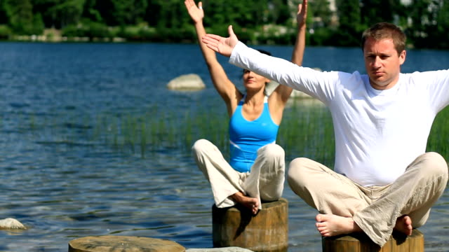 Couple meditating with yoga by the lake, tracking shot video