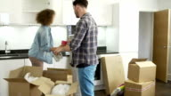 Couple Moving Into New Home And Unpacking Boxes video