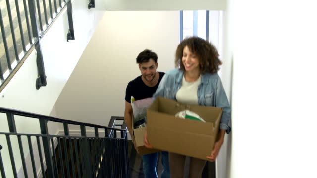 Couple Moving Into New Home Carrying Box Upstairs video