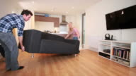 couple moving sofa in new home video