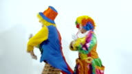 A couple of colorful clowns are dancing a funny dance showing holiday emotions video