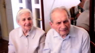 Couple of elderly people seeing film about past times video