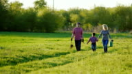 A couple of farmers are walking along a picturesque rural road. With them their little son. Go to plant a tree, carry a shovel and watering pad video