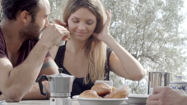 Couple of happy man and woman friends smile, laugh and drink coffee during italian breakfast in natural rural scenic outdoor during summer sunny day morning in tuscany - slow-motion HD video footage video