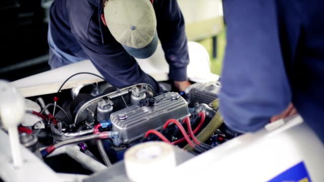 Couple of mechanics working car engine video