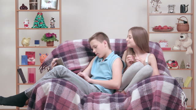 Couple of teenagers enjoying free-time together, sitting in cosy armchair video