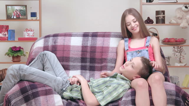Couple of teenagers resting, boy liying down on girls knees. video