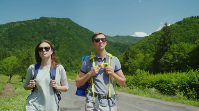 A couple of tourist couple walks along the road to beautiful mountains covered with forest. Active way of life and vacation video