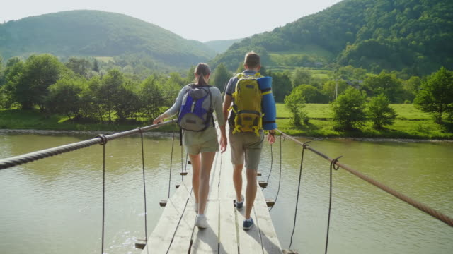 A couple of tourists walk with caution over a unsteady bridge over a mountain river. Rear view, steadicam shot video