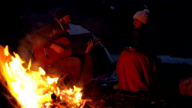 Couple of travelers at dusk near a campfire video