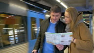 Couple of travelers with map in subway video
