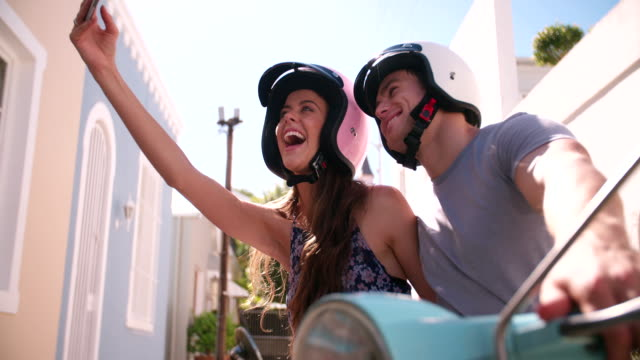 Couple on a scooter taking a selfie video
