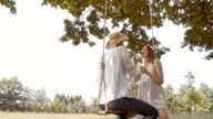 SLO MO Couple on a swing laughing and blowing bubbles video