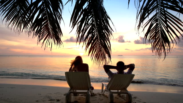 Couple on a tropical beach are admiring the sunset. video
