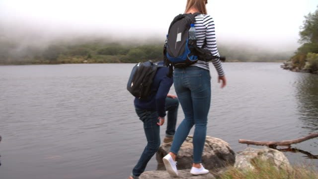 Couple on a walk taking a break by the edge of a lake video