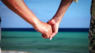 Couple on beach holding hands video