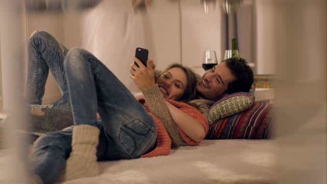 Couple on carpet watching photos on smartphone video