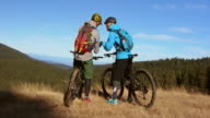 Couple on mountain bikes discussing their position video