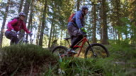 SLO MO Couple on mountain bikes riding up forest trail video