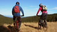 SLO MO Couple on mountain bikes stopping and doing a high five video