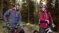 Couple on mountain bikes stopping on forest trail while talking video