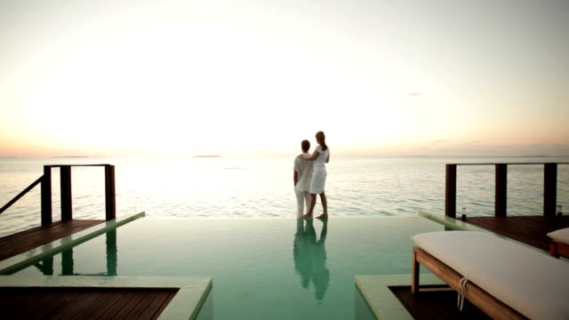 couple on private pool watching sunset video