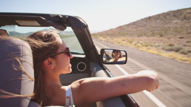 Couple On Road Trip Driving In Convertible Car Shot On R3D video
