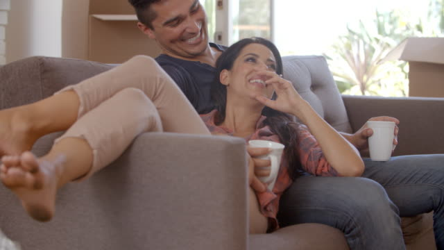 Couple On Sofa Taking A Break From Unpacking On Moving Day video