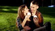 Couple on the grass eating cakes and having fun video