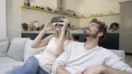 Couple on the sofa and girlfriend wearing VR glasses video