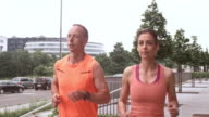 SLO MO TS Couple on their morning run through city video
