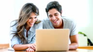 Couple online on a laptop at home video