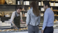 Couple ordering from the bakery counter and salesman serving video