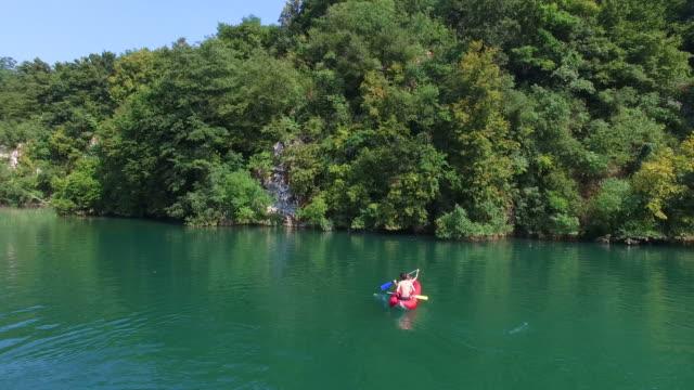 Couple paddling canoe on river on Mreznica river, Croatia video