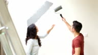Couple painting wall with paint roller and kissing video