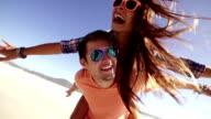 Couple piggyback on beach video