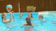 SLO MO Couple playing ball with kids in the pool video