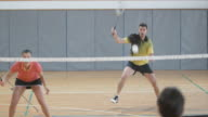 Couple playing doubles indoor badminton scoring a point video