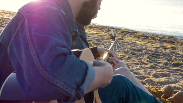 Couple playing guitar on the beach during sunset or sunrise, slow motion video