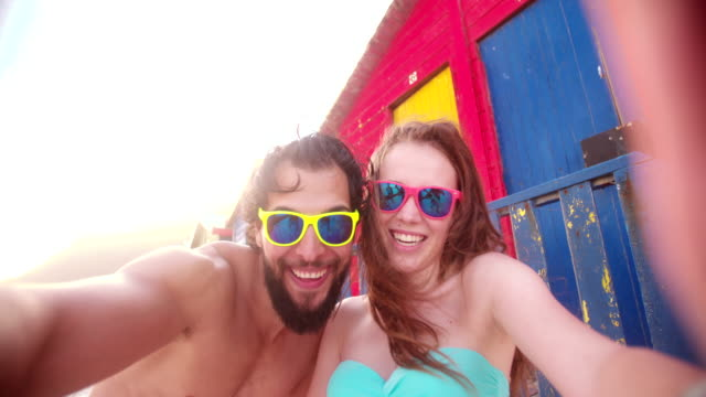 Couple posing for selfie in front of colourful beach huts video