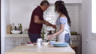 Couple preparing food together by the oven, shot on R3D video